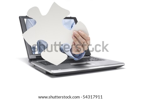 a hand reaches out of a laptop with pieces of puzzle - stock photo