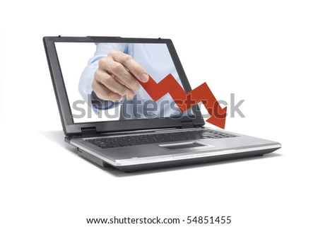 A Hand reaches out of an Laptop with a downwards graph - stock photo