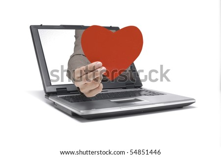 A Hand reaches out of an Laptop with a heart shape - stock photo