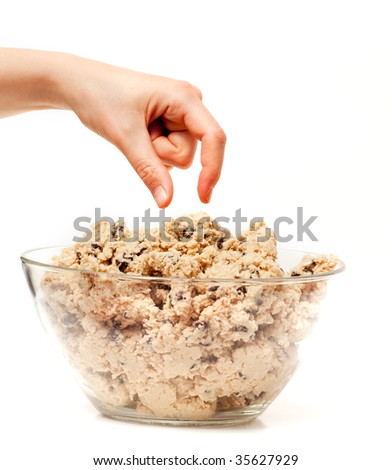 A hand reaching for a bowl of raw cookie dough - stock photo