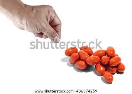 A hand reaching out to pick up antibiotic pills.  - stock photo
