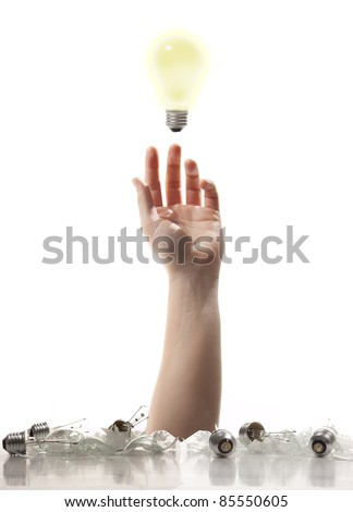 A Hand reaching up from a pile of broken light bulbs trying to grab that one good idea. - stock photo