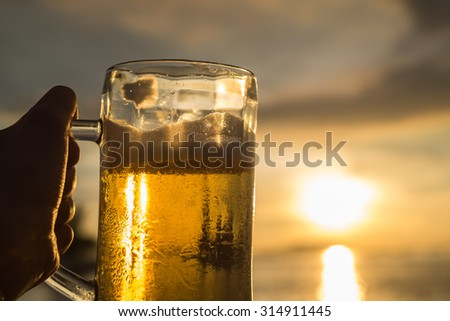 A hand's holding a really cold Beer in the mug with the sunlight shine on the sea background (Selective Focus Point) - stock photo