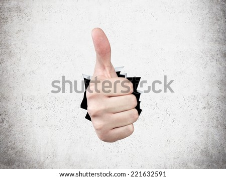 A hand shows thumbs up, Concrete background.frffffff.   - stock photo