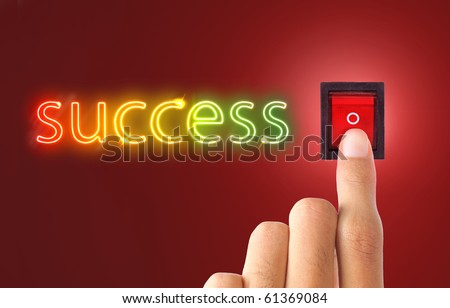 a hand switching on success light. a text of success made of colorful neon - stock photo