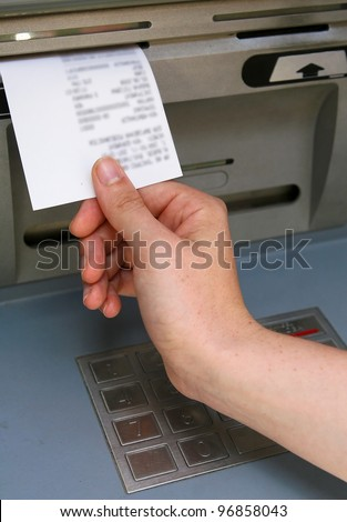 A hand taking a receipt of an Automated Teller Machine, information on the receipt is blurred by photo-editing software.