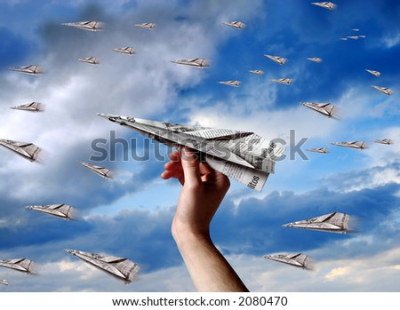 a hand throwing a paper plane to join others planes - stock photo