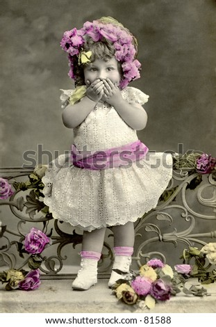 A hand-tinted vintage photograph (c. 1900) of a shy little girl in lacy dress, and with flowers in her hair - used originally as a Valentine's greeting. - stock photo