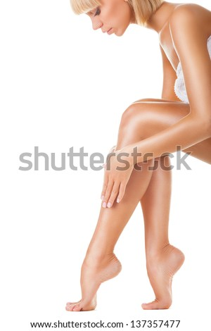 A hand touching beautiful woman's legs isolated on white background