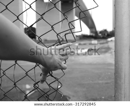 a hand trying to break through the fence in black and white