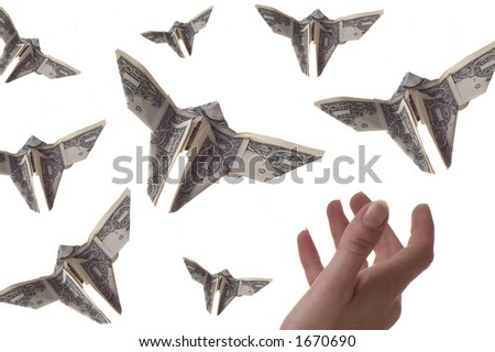 A hand trying to catch dollar bills shaped like butterflies. The background is white. - stock photo