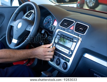 A hand tuning the car radio - stock photo