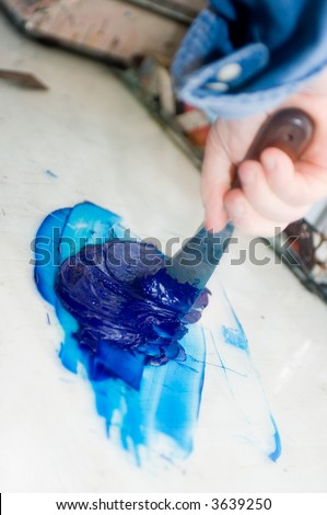 A hand using a filling knife to mix inks for the offset printing process - stock photo