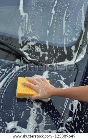 A Hand washing a car with a sponge - stock photo