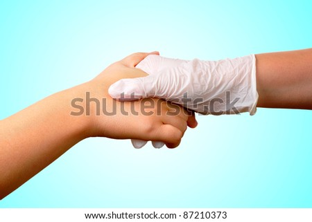 A hand with a medical latex glove holds another hand - stock photo