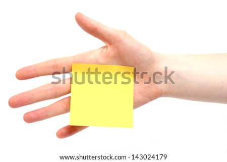A hand with a yellow sticky note on plain background - the note is blank.