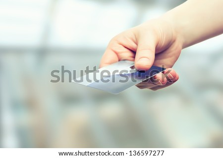 A hand with bank credit plastic card