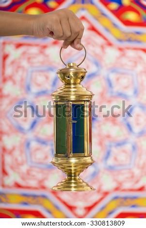 A Hand with Ramadan Lantern over Ramadan Fabric - stock photo