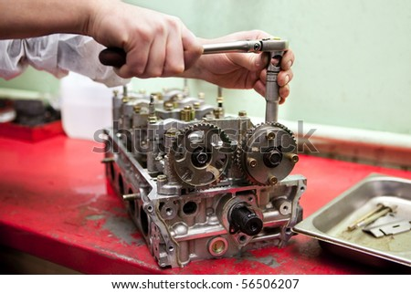 a hand with the wrench is repairing an engine - stock photo