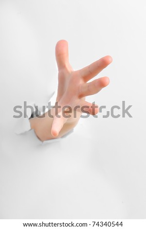 A hand with thumb up popping through a paper - stock photo