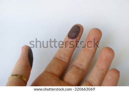 A hand with with black ink on the fingerprint - stock photo