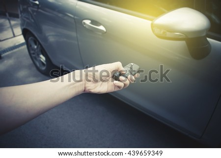 A hand women holding a car's remote control pointing to the door with sunrise - stock photo