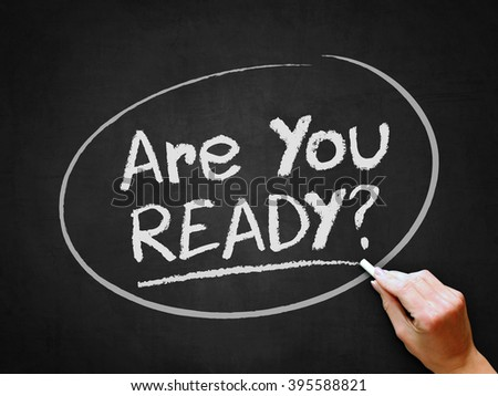 A hand writing 'Are You Ready?' on chalkboard. - stock photo