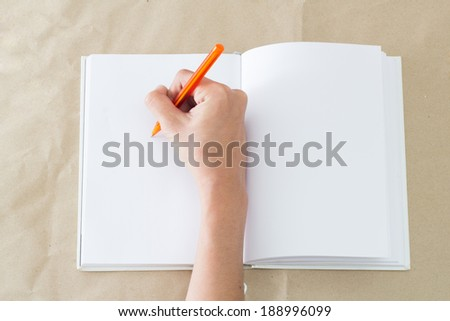 a hand writing on notebook. - stock photo
