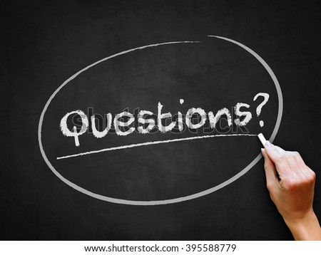 A hand writing 'Questions?' on chalkboard. - stock photo