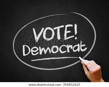 A hand writing 'Vote Democrat' on chalkboard. - stock photo