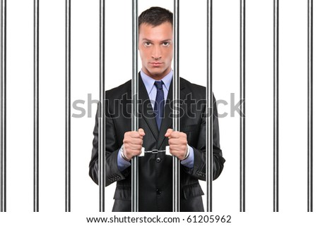 A handcuffed businessman in jail holding bars isolated on white