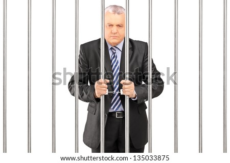 A handcuffed manager in suit posing in jail and holding bars, isolated on white background - stock photo