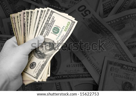 A handful of cash.  The money has selective color, and the rest of the image is in black and white - plenty of copy space. - stock photo