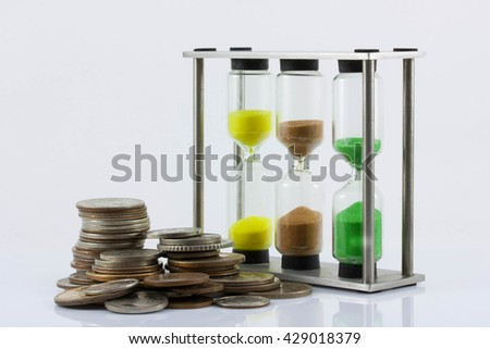 a handful of coins and hourglass on a white background. The increase in the price of labour, the growth of the man-hour cost, time cost, inflation, crisis, isolated - stock photo