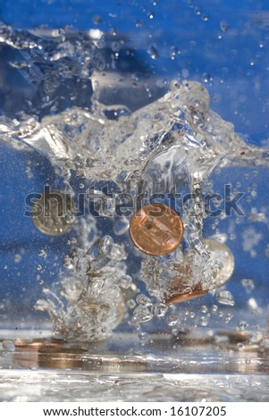A handful of coins dropping into some water. - stock photo
