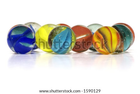 A handful of colorful glass cat-eye marbles on a white background.