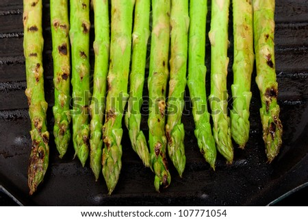 a handful of green asparagus cooking and steaming  on grill plate
