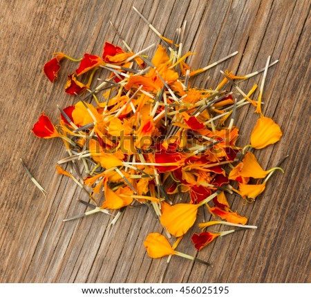 a handful of marigold petals scattered on the old board in the cracks. view from above close-up