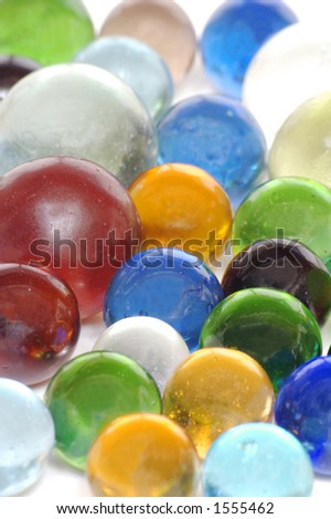 "A handful of multi-colored transparent ""clearie"" marbles on a white background. - stock photo"