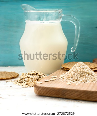 a handful of oatmeal, oat bran, thin wafers and a carafe of milk on a wooden board - stock photo