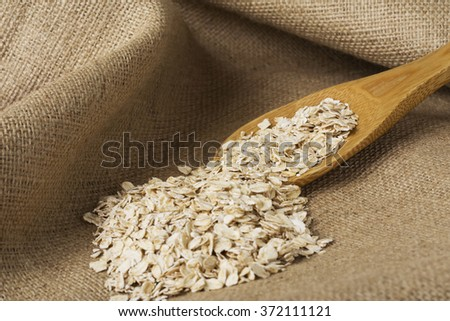 a handful of oatmeal on the background of sackcloth