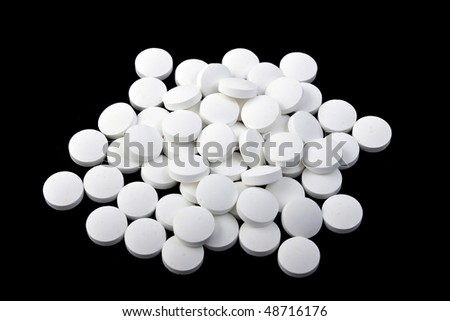 A handful of pills on a black background, isolated - stock photo