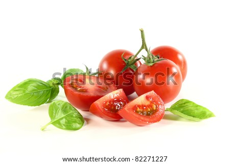 a handful of tomatoes and basil on white background