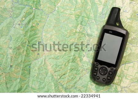 A handheld GPS unit sits on a topo map.  The blank screen is ready for your text. - stock photo