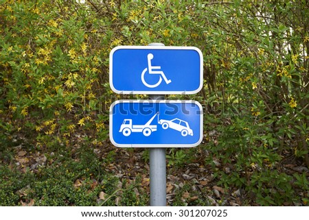 A handicap parking sign and car removal sign on green background - stock photo