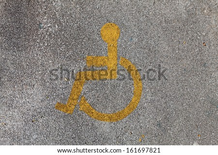A handicap wheelchair man symbol imprinted on a grungy pebble pavement.  - stock photo