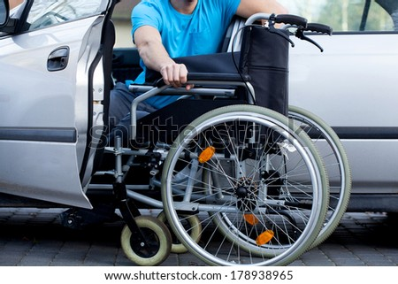 A handicapped car driver with a wheelchair - stock photo