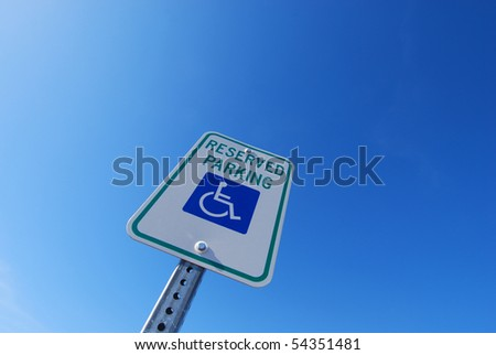 "A ""Handicapped Parking"" sign shot from a dynamic angle against a brilliant blue sky.  Enough space for your ad copy. - stock photo"
