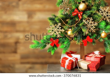 A handmade green Christmas tree and presents on wooden wall background, close-up