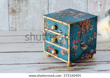 A handmade mini chest of three drawers decoupaged with blue floral vintage paper and gold leaf - stock photo
